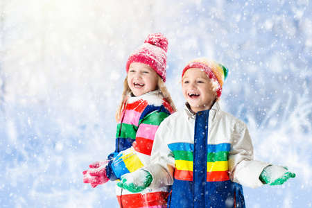Kids playing in snow. Children play outdoors on snowy winter day. Boy and girl catching snowflakes in snowfall storm. Brother and sister throwing snow balls. Family Christmas vacation activity. Banque d'images