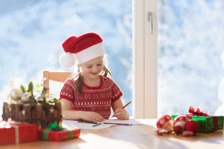 Child writing letter to Santa on Christmas eve. Kids write Xmas present wish list. Little girl sitting in decorated living room with big window on sunny winter day in the mountains, snow outside.