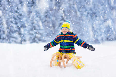 Little boy enjoying a sleigh ride. Child sledding. Toddler kid riding a sledge. Children play outdoors in snow. Kids sled in the Alps mountains in winter. Outdoor fun for family Christmas vacation. Stockfoto - 134395004