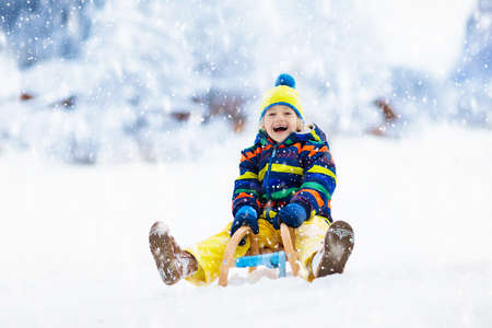 Little boy enjoying a sleigh ride. Child sledding. Toddler kid riding a sledge. Children play outdoors in snow. Kids sled in the Alps mountains in winter. Outdoor fun for family Christmas vacation. Stockfoto - 134395011