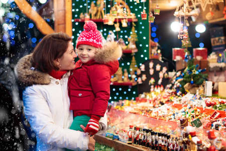 Mother and child in warm hat watching handmade glass Christmas tree ornaments at traditional German Xmas street market. Family with child shopping for Christmas presents on winter fair on snowy day.