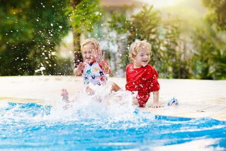 Child playing in swimming pool. Summer vacation with kids. Little boy jumping into water during exotic holiday in tropical island resort. Active outdoor sport for preschooler. Stockfoto - 134395044