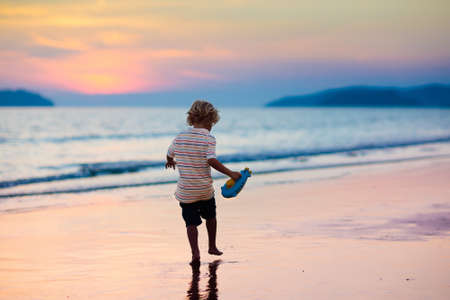 Child playing on ocean beach. Kid jumping in the waves at sunset. Sea vacation for family. Little boy running on exotic island during summer holiday. Stockfoto