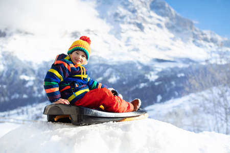 Little boy enjoying a sleigh ride. Child sledding. Toddler kid riding a sledge. Children play outdoors in snow. Kids sled in the Alps mountains in winter. Outdoor fun for family Christmas vacation. Stockfoto - 134395104