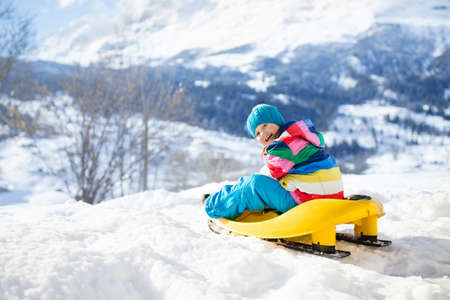 Little girl enjoying a sleigh ride. Child sledding. Toddler kid riding a sledge. Children play outdoors in snow. Kids sled in the Alps mountains in winter. Outdoor fun for family Christmas vacation. Stockfoto - 134395114