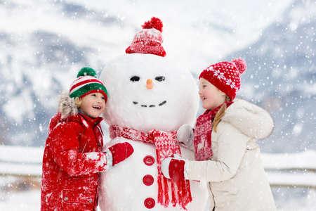 Dziecko budynku bałwana. Dzieci budują człowieka śniegu. Chłopiec i dziewczynka bawi się na świeżym powietrzu w mroźny zimowy dzień. Rodzinna zabawa na świeżym powietrzu na Boże Narodzenie w górach. Dzieci bawią się w szwajcarskim krajobrazie górskim. Zdjęcie Seryjne