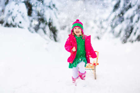 Little girl enjoying a sleigh ride. Child sledding. Toddler kid riding a sledge. Children play outdoors in snow. Kids sled in the Alps mountains in winter. Outdoor fun for family Christmas vacation. Stockfoto