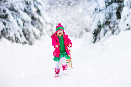Little girl enjoying a sleigh ride. Child sledding. Toddler kid riding a sledge. Children play outdoors in snow. Kids sled in the Alps mountains in winter. Outdoor fun for family Christmas vacation. Stockfoto - 134395157