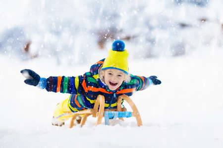 Little boy enjoying a sleigh ride. Child sledding. Toddler kid riding a sledge. Children play outdoors in snow. Kids sled in the Alps mountains in winter. Outdoor fun for family Christmas vacation. Stockfoto - 134395178