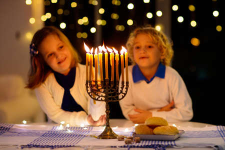 Kids celebrating Hanukkah. Jewish festival of lights. Children lighting candles on traditional menorah. Boy in kippah with dreidel and Sufganiyah doughnut. Israel holiday. Stock Photo