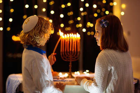 Kids celebrating Hanukkah. Jewish festival of lights. Children lighting candles on traditional menorah. Boy in kippah with dreidel and Sufganiyah doughnut. Israel holiday.