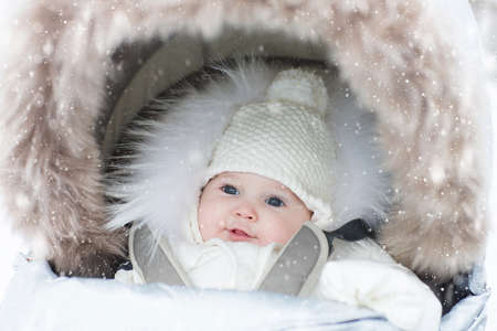 Baby in stroller in winter snow. Kid in pram. Child wearing warm jacket and knitted hat wrapped in foot muff for comfort on stroll in snowy park. Outdoor fun and travel with infant by any weather.