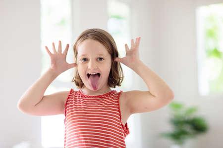 Enfant faisant la grimace. Kid taquiner et rire. Petite fille idiote jouant et souriant.