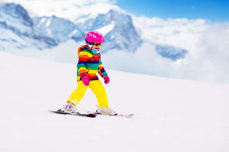 Kinderskifahren in den Bergen. Aktives Kleinkind mit Schutzhelm, Schutzbrille und Stöcken. Skirennen für kleine Kinder. Wintersport für die Familie. Kinderskikurs in der Alpinschule. Kleiner Skifahrer, der im Schnee läuft