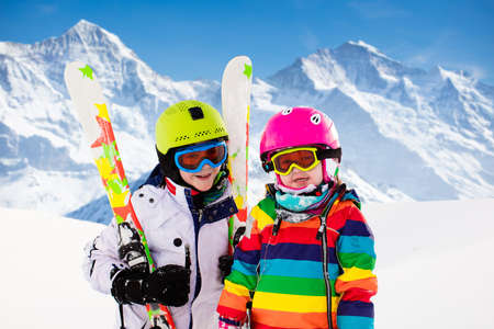 Kinderskifahren in den Bergen. Aktive Kinder mit Schutzhelm, Schutzbrille und Stöcken. Skirennen für kleine Kinder. Wintersport für die Familie. Kinderskikurs in der Alpinschule. Kleiner Skifahrer, der im Schnee läuft