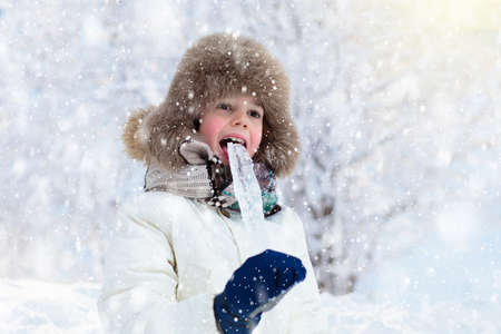 Bambino che gioca con la neve in inverno. Ragazzino in giacca calda e cappello lavorato a maglia che cattura i fiocchi di neve nel parco invernale a Natale. I bambini giocano nella foresta innevata. Divertimento all'aria aperta per i bambini durante la stagione fredda.