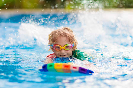 Child learning to swim in outdoor pool of tropical resort. Kids learn swimming. Exercise and training for young children. Little boy with colorful float board in sport club. Swimming baby or toddler.