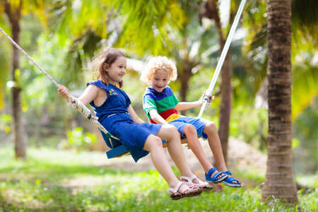 Kids on swing. Children swinging on playground in tropical resort with coconut palm trees. Summer beach fun. Family vacation in Asia. Boy and girl playing outdoor. Foto de archivo