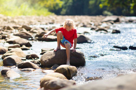Children hiking in Alps mountains crossing river. Kids play in water at mountain in Austria. Spring family vacation. Little boy and girl on hike trail. Outdoor fun. Active recreation with children. Stockfoto - 140321545