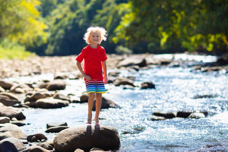 Children hiking in Alps mountains crossing river. Kids play in water at mountain in Austria. Spring family vacation. Little boy and girl on hike trail. Outdoor fun. Active recreation with children. Stockfoto - 140409818