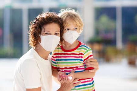 Famille avec enfants en masque facial dans un centre commercial ou à l'aéroport. La mère et l'enfant portent un masque facial pendant l'épidémie de virus et de grippe. Protection contre les virus et les maladies, désinfectant pour les mains dans un lieu public bondé.