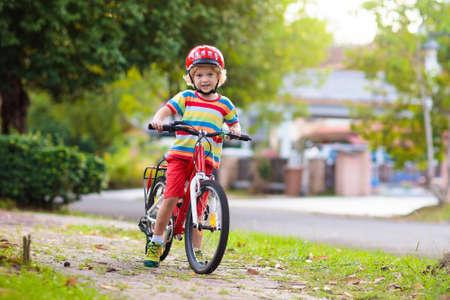 Enfants à vélo dans le parc. Les enfants vont à l'école et portent des casques de vélo sécuritaires. Petit garçon faisant du vélo le jour d'été ensoleillé. Sport de plein air sain et actif pour jeune enfant. Activité amusante pour enfant