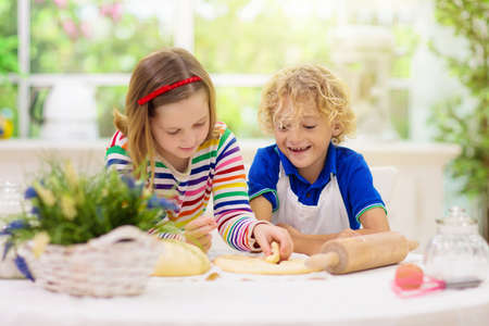 Kids baking pie in white sunny kitchen. Children cooking dinner. Boy and girl rolling dough at big window. Healthy nutrition for child. Brother and sister playing at home. Archivio Fotografico