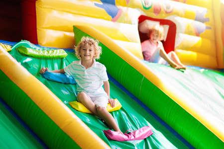 Kind springt auf buntes Spielplatztrampolin. Kinder springen in aufblasbare Hüpfburg auf Kindergarten-Geburtstagsfeier Aktivitäts- und Spielzentrum für Kleinkinder. Kleiner Junge, der im Sommer draußen spielt.