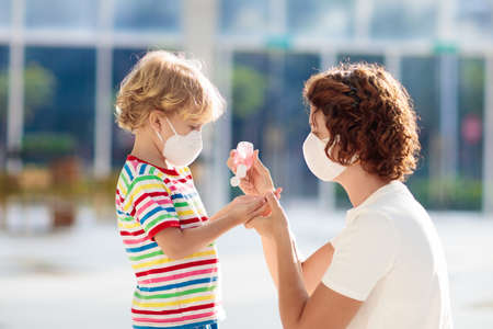 Family with kids in face mask in shopping mall or airport. Mother and child wear facemask during coronavirus and flu outbreak. Virus and illness protection, hand sanitizer in public crowded place. Stock Photo - 140878004