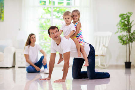 Happy young family with kids at home. Father, mother, daughter and son playing on the floor in living room. Mom, dad, little boy and girl holding pet cat. Parents and children play together. Archivio Fotografico - 140879603
