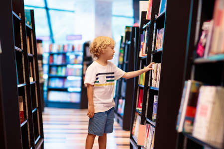 Child in school library. Kids read books. Little boy reading and studying. Children at book store. Smart intelligent preschool kid choosing books to borrow. Zdjęcie Seryjne