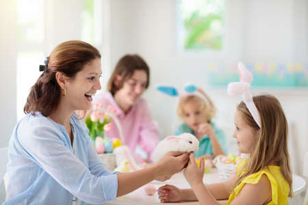 Mother and kids with pet rabbit color Easter eggs. Mom, little girl and boy with bunny ears dying and painting for Easter egg hunt in white sunny room. Family celebration and home decoration in spring Archivio Fotografico