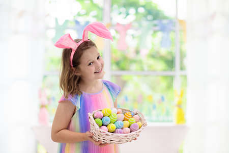 Kids dyeing Easter eggs. Children in bunny ears dye colorful egg for Easter hunt. Home decoration with flowers, basket and rabbit for spring holiday celebration. Little girl decorating home.
