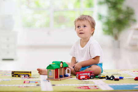 Little boy playing toy cars on play mat. Young kid with colorful educational vehicle and transport toys on carpet. City street map rug. Child driving car to parking garage. Kids at home or daycare. 免版税图像
