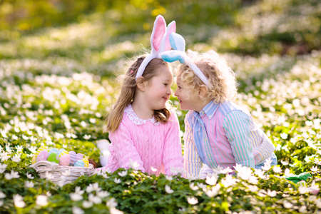 Easter egg hunt in spring garden. Kids searching for colorful eggs and sweets hidden in blooming flower field. Children with bunny ears and egg basket. Family Easter celebration. Boy and girl play.