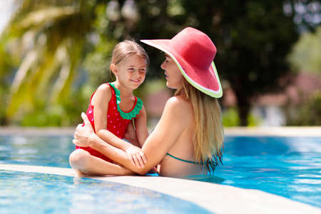 Mother and child at swimming pool. Mom and kid swim in tropical resort. Young woman and little girl in red swimsuit and hat on summer beach vacation. Holiday and travel for family with kids. Foto de archivo