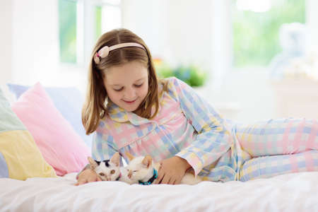 Child playing with baby cat on bed in white bedroom. Kid holding white kitten. Little girl in pajamas with cute pet animal at home. Kids play with cats. Children and domestic animals pets.