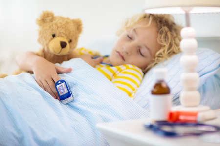 Sick little boy with pulse oximeter on his finger. Asthma treatment. Ill child lying in bed. Unwell kid with chamber inhaler, cough medicine. Flu season. Bedroom or hospital room for young patient.