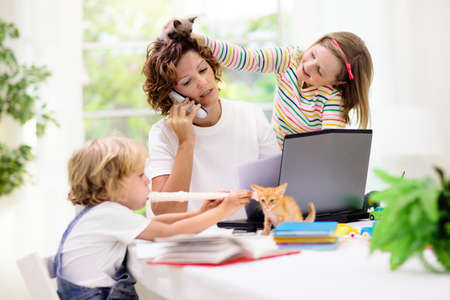 Mother working from home with kids. Quarantine and closed school during coronavirus outbreak. Children make noise and disturb woman at work. Homeschooling and freelance job. Boy and girl playing. Reklamní fotografie - 142657442