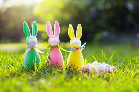 Easter bunny in face mask during coronavirus outbreak. Decoration and celebration during global virus pandemic. Easter egg hunt in flu epdemic. Foto de archivo