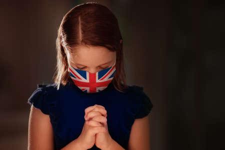 Pray for UK. Child in face mask praying for Great Britain. Little British girl in hospital chapel or church during coronavirus outbreak. Virus pandemic. Kids worship. Children say a prayer. 写真素材