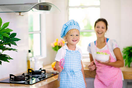 Mother and kid cook in white kitchen. Mom and child cooking at home. Little boy in chef hat and apron and mom cut vegetables for salad. Healthy nutrition for young children. Kids help prepare dinner.