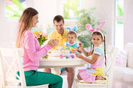 Mother, father and kids color Easter eggs. Mom, dad, little girl and boy with bunny ears dying and painting for Easter egg hunt. Family and child celebration. Home decoration for spring holiday. Stockfoto