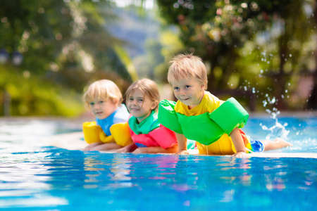 Kids play in outdoor swimming pool of tropical resort. Swim aid for young child. Baby learning to dive. Group of children playing in water. Colorful life jacket. Beach and summer fun.