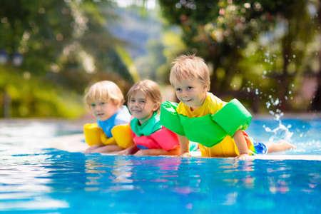 Los niños juegan en la piscina al aire libre del resort tropical. Ayuda de natación para niños pequeños. Bebé aprendiendo a bucear. Grupo de niños jugando en el agua. Chaleco salvavidas colorido. Diversión en la playa y el verano.