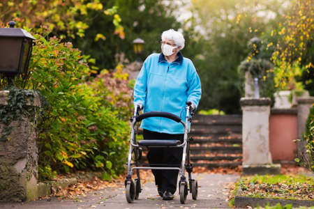 Senior handicapped lady wearing face mask with a walking disability at coronavirus outbreak. Old person in surgical mask pushing walker or wheel chair. Disabled sick patient of nursing home.