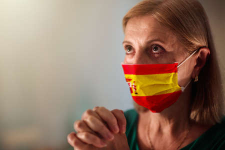 Pray for Spain. Woman in face mask praying. Senior patient in hospital chapel or church during coronavirus outbreak. Virus pandemic. People worship. Spanish nurse saying a prayer for sick patient. Banque d'images