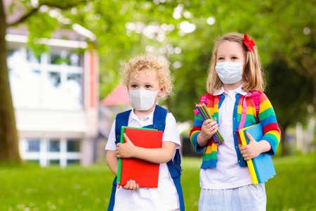 Schulkind, das während des Ausbruchs des Koronavirus und der Grippe eine Gesichtsmaske trägt. Jungen und Mädchen gehen nach Covid-19-Quarantäne und Sperrung wieder zur Schule. Gruppe von Kindern in Masken zur Vorbeugung von Coronaviren.