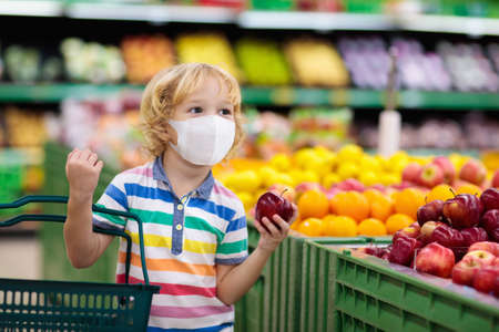 Shopping with kids during virus outbreak. Child wearing surgical face mask buying fruit in supermarket in coronavirus pandemic. Little boy buy fresh vegetable in grocery store. Covid-19 epidemic.