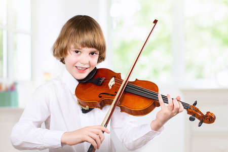 Child playing violin. Remote learning from home. Arts for kids. Little boy with musical instrument. Video chat conference lesson. Online music tuition. Creative children play song. Classical education